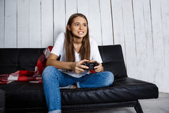 Beautiful girl playing video games, sitting on sofa at home. Royalty Free Stock Images
