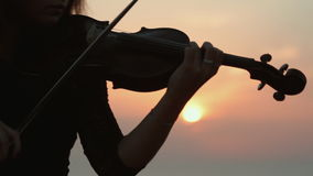 Beautiful girl playing the violin while the sun stock video footage