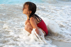 Beautiful girl playing with the waves. Beautiful girl surrounded by waves in the beach Stock Photography