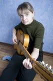 Beautiful girl plays on guitar Stock Photos