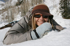 Beautiful girl plays and smiles in the snow. A beautiful active woman smiles in the snow and mountains Stock Photography
