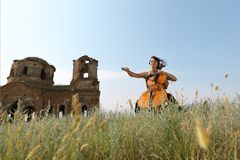 The beautiful girl plays a violoncello. In the field royalty free stock images