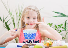 Beautiful girl is pointing at a delicious marshmallow. Royalty Free Stock Photography