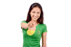 Beautiful girl pointing in front. Focus on the girl, blur on the hand. Stock Photography
