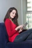 Beautiful girl pointing at ipad. Beautiful girl sitting on a sofa pointing at ipad Stock Photo