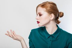 Beautiful girl pointing to the side. Presenting your product. Expressive facial expressions emotions business woman. royalty free stock images