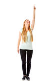 A beautiful girl is pointing up with her hand - isolated on white. Royalty Free Stock Images