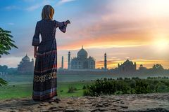 Beautiful girl points to Taj Mahal. Travel concept