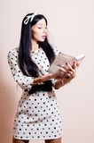 Beautiful girl in polka dot white dress reading Royalty Free Stock Photo