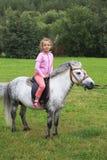 Beautiful girl on a pony. Beautiful girl riding a pony Stock Image