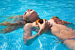 The beautiful girl in pool. The beautiful girl lies in pool with colours Stock Image