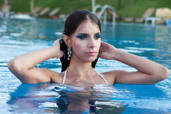 Beautiful girl in a pool. Young woman beauty portrait in water Stock Images