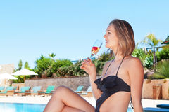 A beautiful  girl by the pool drinking a fruit drink. Summe Stock Image