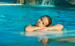 Beautiful Girl in the pool. Beautiful Girl lying on the pool`s ledge Royalty Free Stock Photography