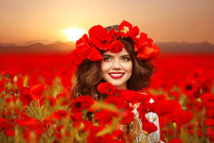 Beautiful girl in poppies field at sunset. Happy smiling teen gi. Rl portrait with red flowers on head enjoying life. Makeup. Carefree woman. Wellness well-being Stock Photos