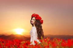 Beautiful girl in poppies field at sunset. Happy smiling teen po Royalty Free Stock Photos