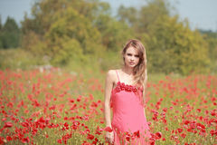 Beautiful Girl in the poppy field, red dress Royalty Free Stock Photo