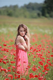 Beautiful Girl in the poppy field, red dress Stock Photos