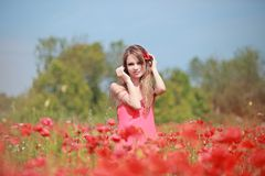 Beautiful Girl in the poppy field, red dress Royalty Free Stock Image