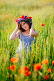 Beautiful girl in the poppy flowers field Royalty Free Stock Photography