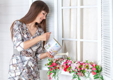 Beautiful girl on the porch with white lantern, decorated flowers. Beautiful girl on the porch with a white lantern, decorated with flowers. Spring stock photography