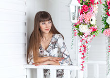 Beautiful girl on the porch with white lantern, decorated flowers. Beautiful girl on the porch with a white lantern, decorated with flowers. Spring stock images
