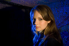 Beautiful girl portrait. High contrast portrait of a young beautiful female with a blue urban background Stock Photo