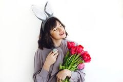 Beautiful girl portrait with bunny ears holding easter egg and tulips on white background indoors, space for text. Easter hunt. Concept,spring seasonal stock photography