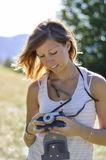 Beautiful girl portrait at the field holding a retro camera. Low Stock Photos