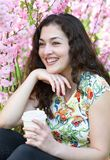 Beautiful girl portrait outdoor, sitting near bush with pink flowers, cup of coffee stock images