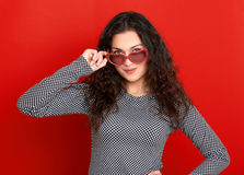 Beautiful girl portrait posing and flirting on red background, long curly hair, sunglasses in heart shape, glamour concept Royalty Free Stock Image