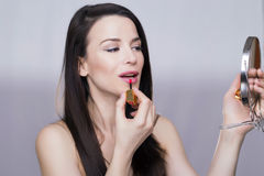 Beautiful girl. Portrait of a girl putting on lipstick with mirror Stock Photo