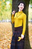 Beautiful girl portrait standing near tree trunk in autumn outdoor, city park with yellow leaves on background, fall season Royalty Free Stock Photography