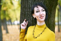 Beautiful girl portrait standing near tree trunk in autumn outdoor, city park with yellow leaves on background, fall season Stock Images
