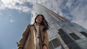 Beautiful asian girl posing against a high building and beautiful sky