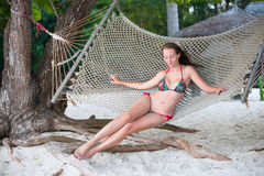 Beautiful girl poses in hammock on the beach Royalty Free Stock Image