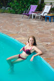 Beautiful girl poses in the swimming pool Stock Photography