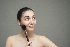 Beautiful girl posing with a big cosmetic brush. Royalty Free Stock Image