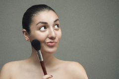 Beautiful girl posing with a big cosmetic brush. Stock Photography