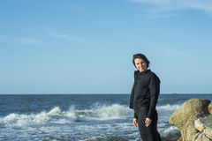 Beautiful girl posing in a black suit. Near the sea Royalty Free Stock Photo