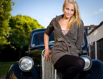 Beautiful girl posing with a black vintage car. Beautiful young blond girl standing in front of a black vintage car royalty free stock images