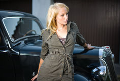 Beautiful girl posing with black vintage car. Beautiful young blond girl standing in front of a black vintage car stock image