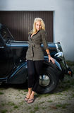 Beautiful girl posing with a black vintage car. Beautiful young blond girl standing in front of a black vintage car royalty free stock photo