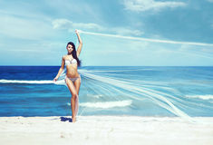 Beautiful girl posing with a blowing silk. Beach, sea and sky ba Royalty Free Stock Photo