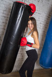 Beautiful girl posing in boxing gloves. She fulfills blows in the gym Royalty Free Stock Photo
