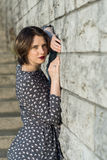 Beautiful girl posing in a dress. Near the wall Stock Photography