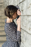 Beautiful girl posing in a dress. Near the wall Stock Images