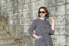 Beautiful girl posing in a dress. Near the wall Royalty Free Stock Photo