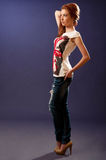 Beautiful girl posing for fashion shoot. Beautiful red hair girl posing for fashion shoot wearing heels and flag design on tshirt Stock Images