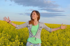 Beautiful girl posing in a field of yellow flowers Royalty Free Stock Photos